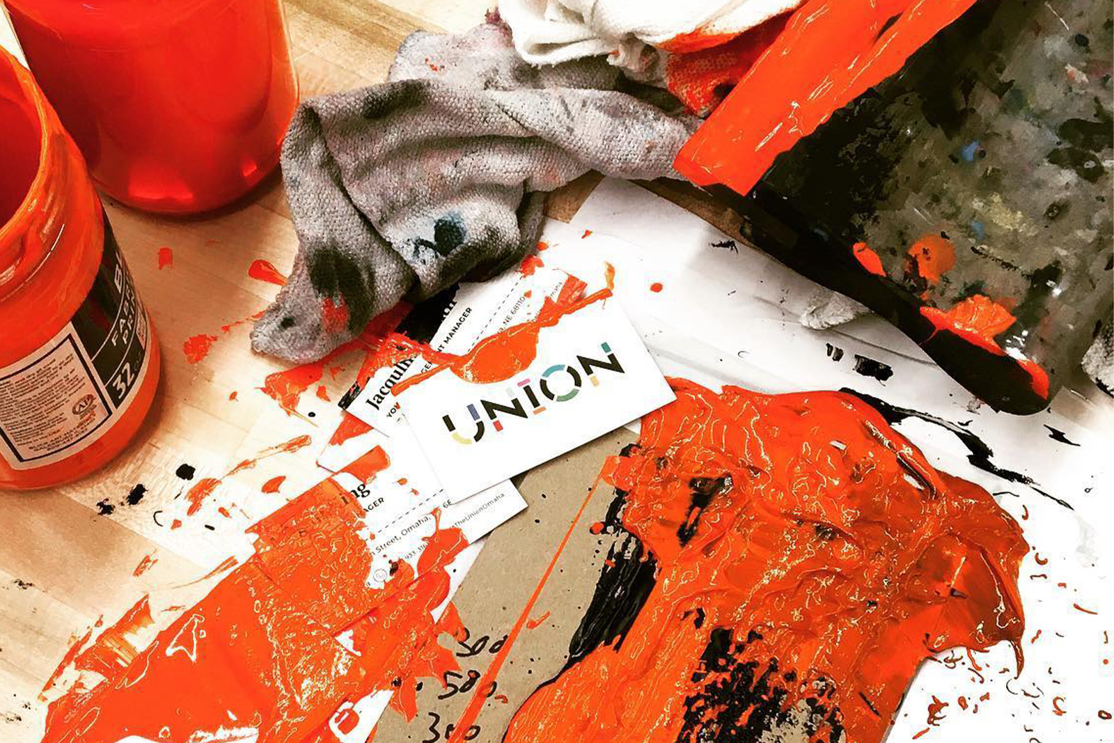 Co Op Distanced Membership Orange screen printing ink covers a messy work station that also inlcudes a blackened rag ink covered squeegie and Union business cards