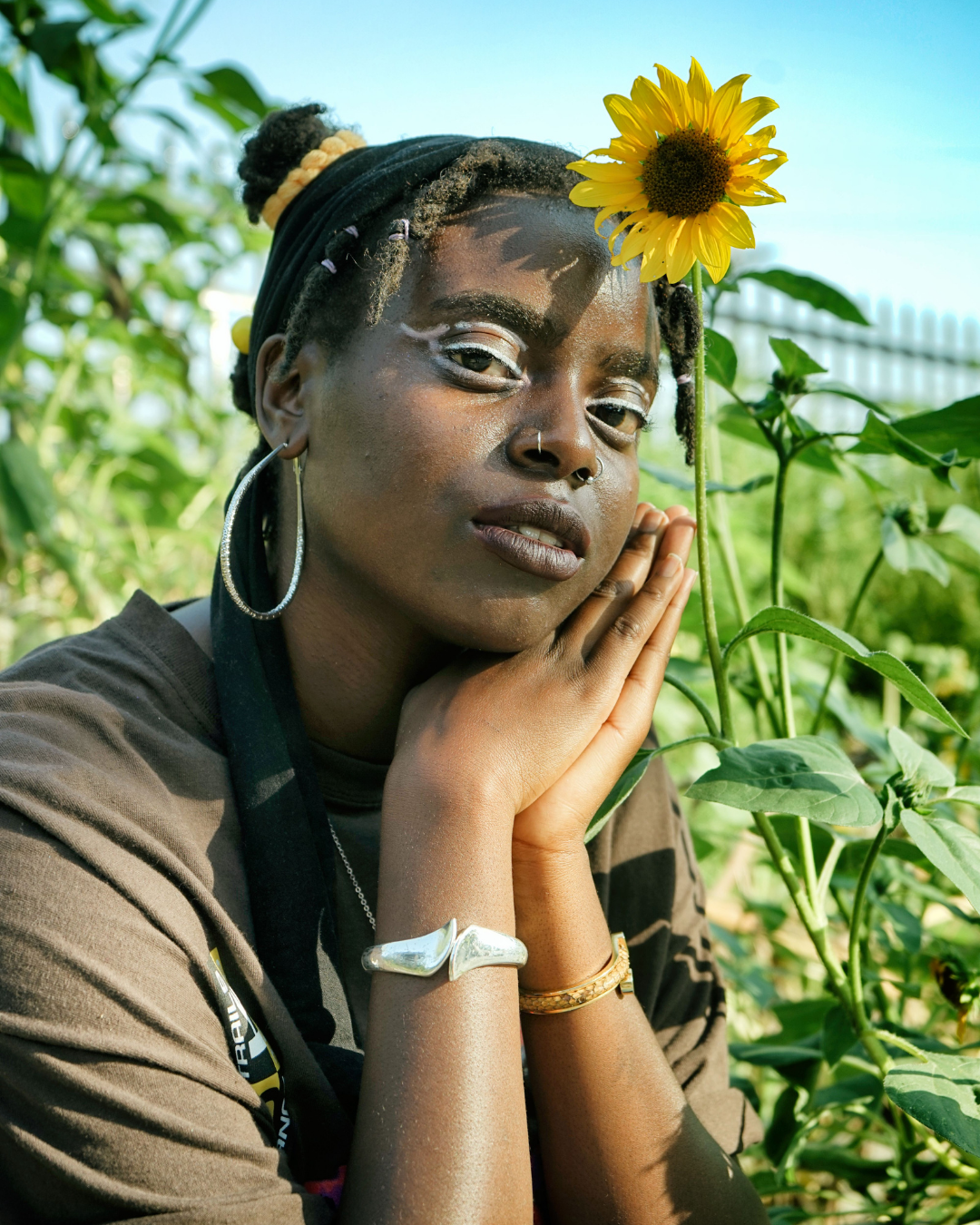 Portrait of Alajia Mc Kizia in a garden her hands near her face sitting next to a sunflower