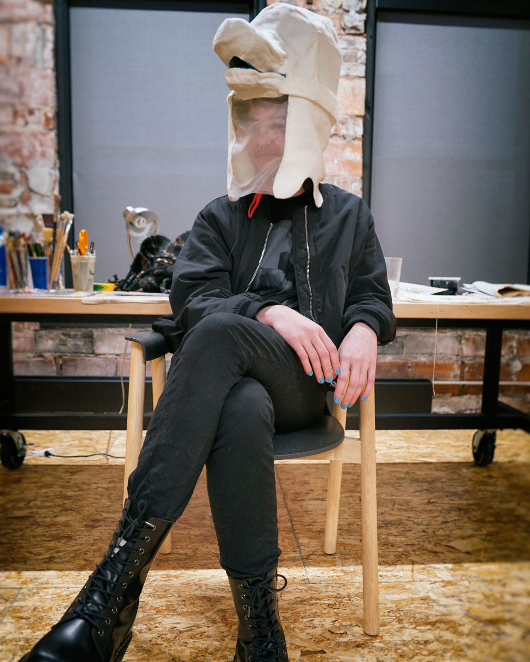 Portrait of Michael Johnson sitting in his Union studio wearing a fabric Wiggle Bird mask on his head