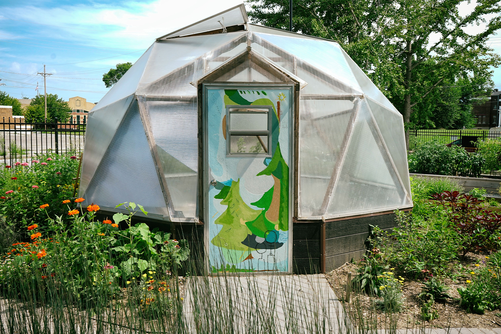 Abundance garden - photo of geodesic dome in Union garden. The garden is blooming with flowers and grasses and the door of the dome is painted with a bright, abstract nature scene.