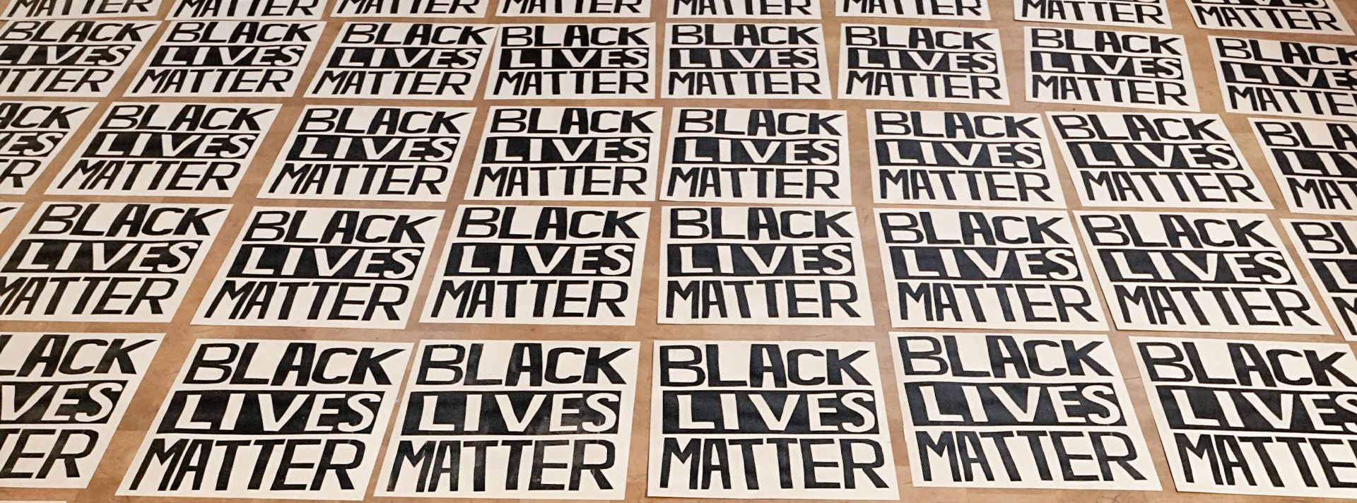 Hundreds of black lives matter posters laying on the wanda d ewing gallery floor