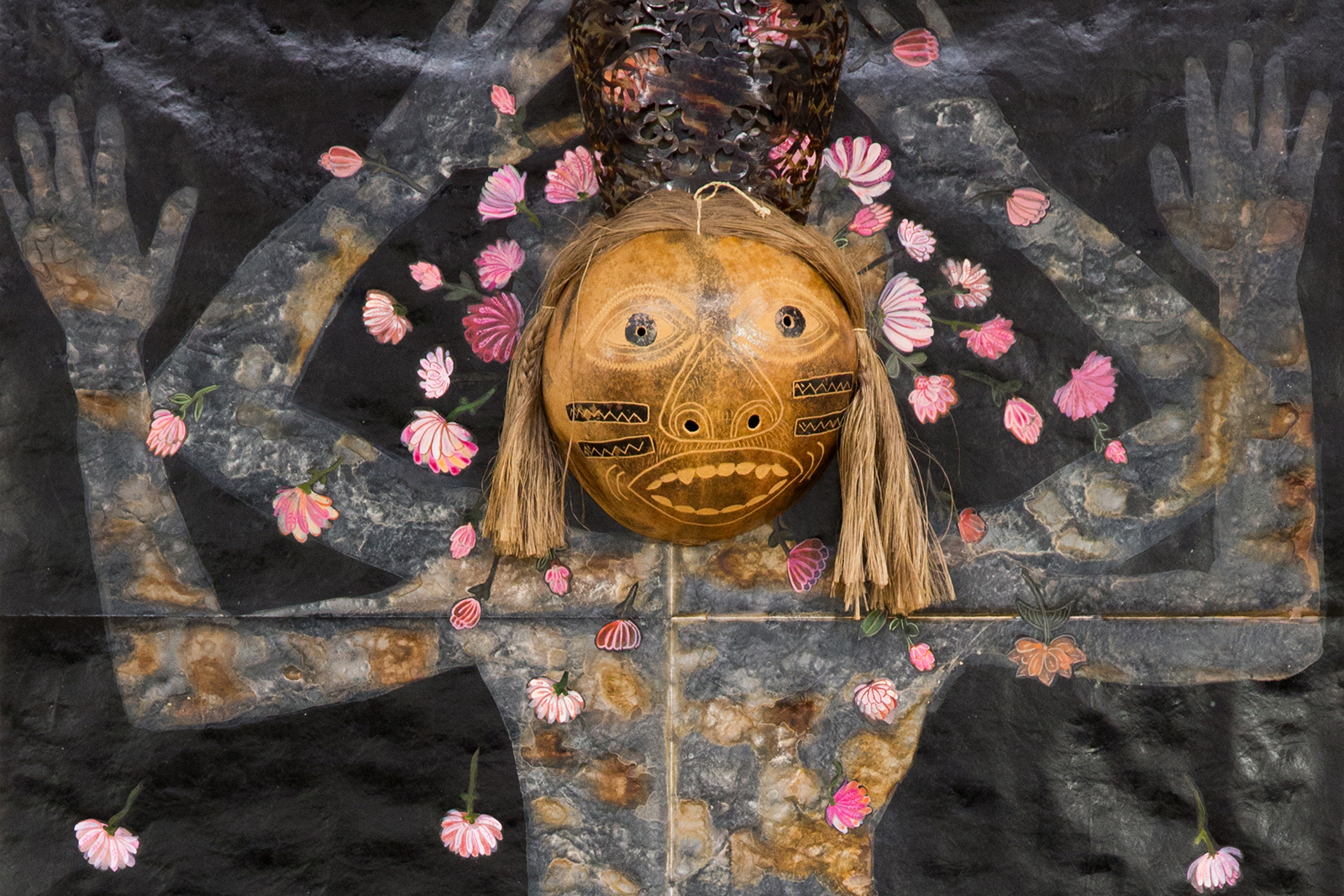 "Mixed media work of human figure from ""River"" by Nancy Friedemann-Sánchez, featuring a carved wooden head and arms painted with flowers."