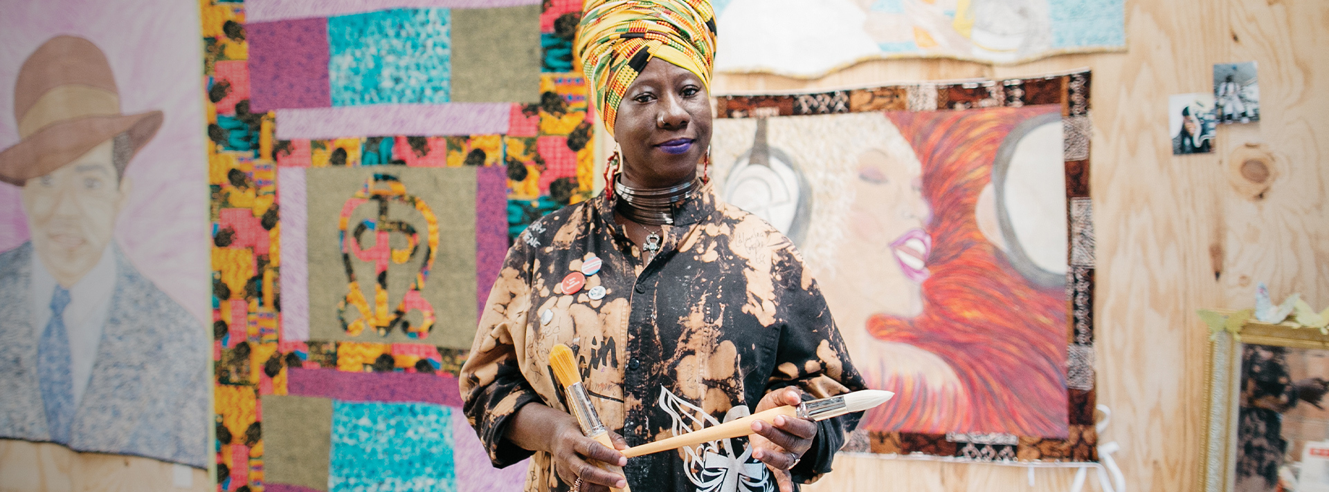 2017 Union Fellow Celeste Butler stands in front of two of her large quilts. She wears a yellow patterned head wrap and artist's smock, holding two paintbrushes. (Union fellowship header)